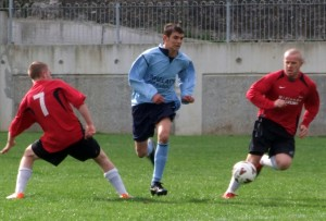 Ballyroan FC's Jamie Whelan flies between Dynamo Town pair Joe Brophy and Killian Doyle